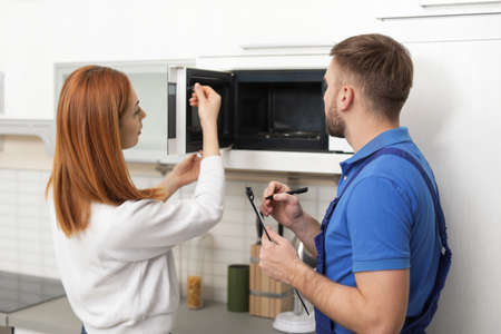 Housewife and repairman near microwave oven in kitchen 写真素材