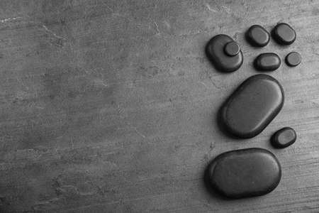Zen stones on grey background, top view with space for text