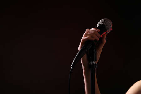 Woman holding microphone on black background, closeup. Space for text Stock Photo