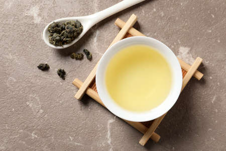 Cup of Tie Guan Yin oolong and spoon with tea leaves on color background, top view
