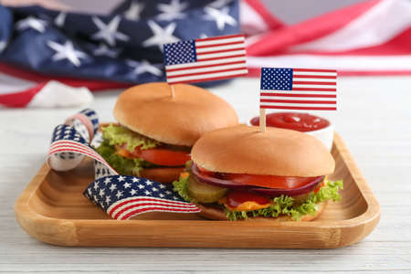 Tasty burgers with USA flags and sauce on table. Traditional American food