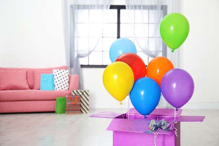 Gift box with bright air balloons in living room. Space for text