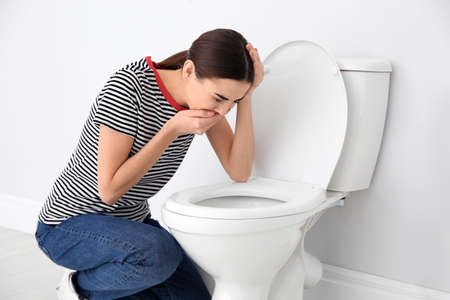 Young woman suffering from nausea over toilet bowl indoors Stock Photo