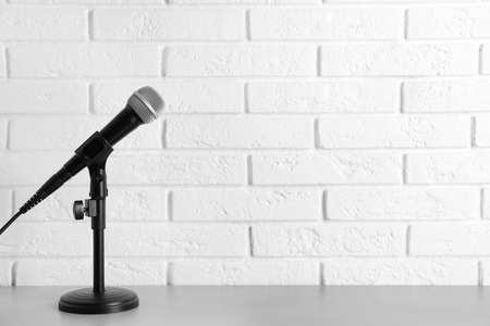Modern microphone on table near brick wall. Space for text