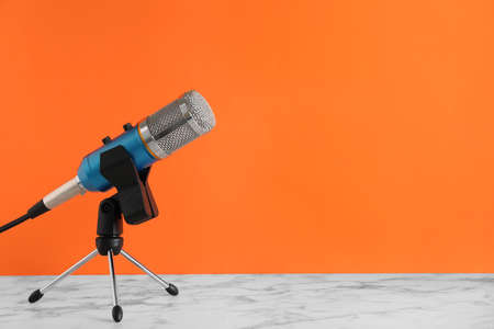 Microphone on table against color background. Space for text
