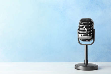 Retro microphone on table against color background. Space for text