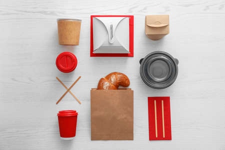 Flat lay composition with paper bag and different takeaway items on wooden background. Space for design 免版税图像