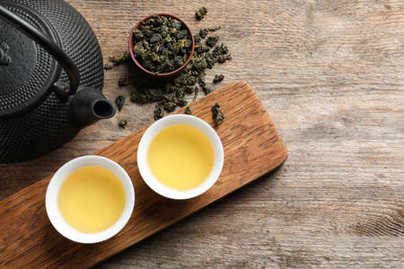 Cups and teapot of Tie Guan Yin oolong on wooden background, top view with space for text