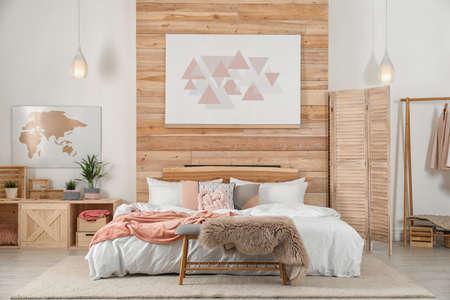 Interno elegante della stanza con un letto comodo vicino alla parete di legno Archivio Fotografico