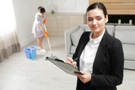 Responsabile delle pulizie che controlla il lavoro di pulizia nella camera d'albergo Archivio Fotografico