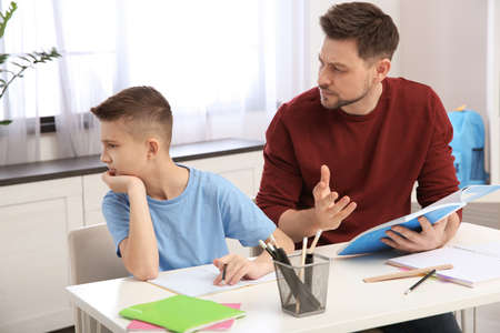 Dad helping his son with difficult homework assignment in room