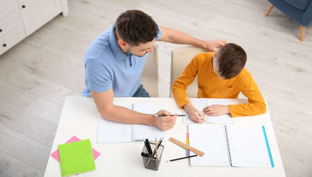 Dad helping his son with homework in room, above view Standard-Bild