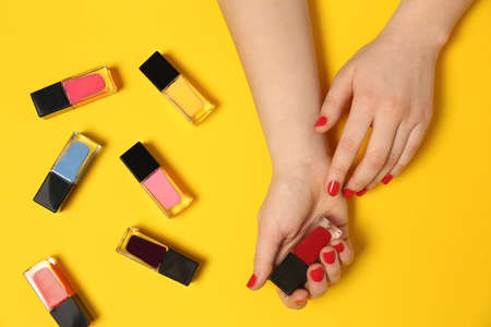 Woman with red manicure and nail polish bottles on color background, top view