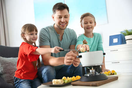 Children enjoying fondue dinner with father at home
