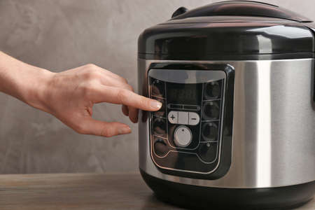 Woman turning on modern electric multi cooker on grey background, closeup