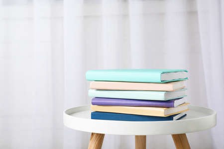 Stack of books on table against curtain. Space for text