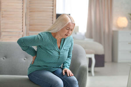 Senior woman suffering from back pain at home Stockfoto
