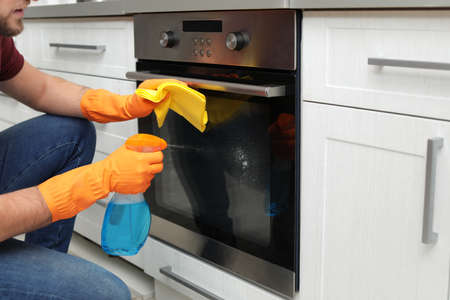 Young man cleaning oven with rag and detergent in kitchen, closeup