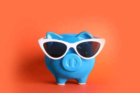 Piggy bank with sunglasses on color background. Travel agency