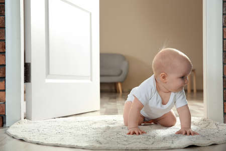 Cute little baby crawling on rug indoors, space for text