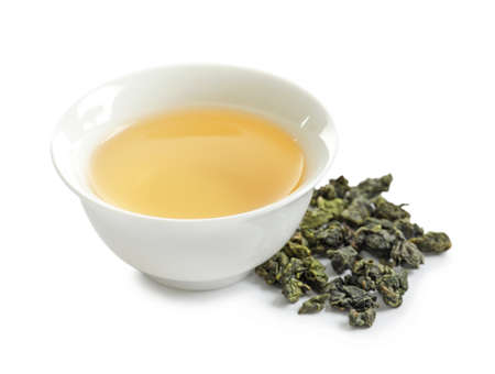 Cup of Tie Guan Yin oolong and tea leaves on white background 版權商用圖片