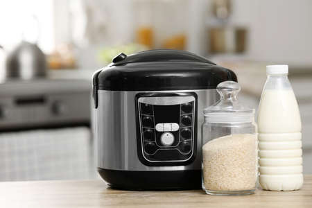 Modern electric multi cooker, rice and milk on table in kitchen Imagens