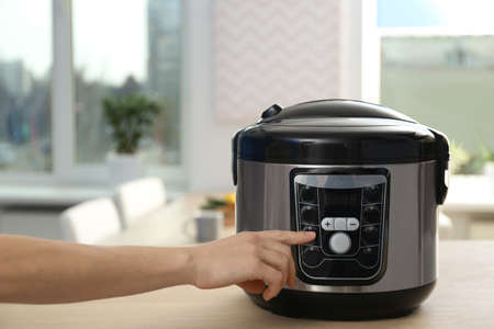 Woman turning on modern electric multi cooker in kitchen