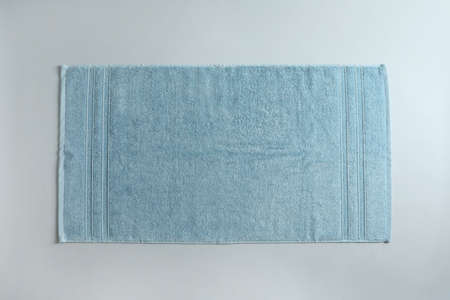 Fresh fluffy towel on grey background, top view. Mockup for design