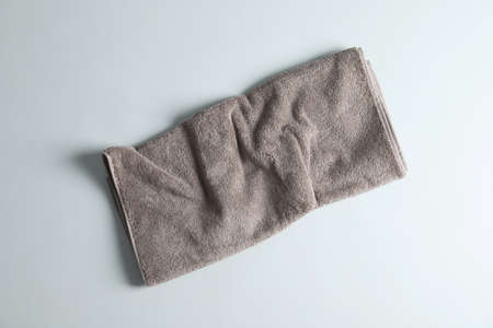 Fresh fluffy towel on grey background, top view Stock Photo
