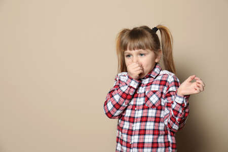 Cute little girl coughing against color background. Space for text