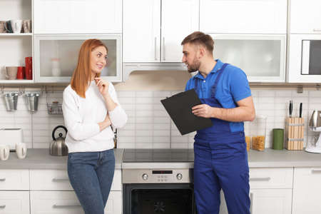 Housewife with repairman near modern oven in kitchen Banco de Imagens