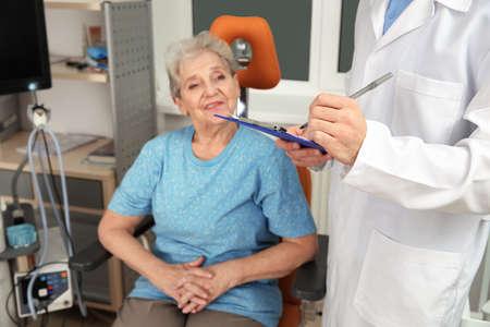 Senior woman visiting otolaryngologist in clinic. Hearing aid Stock Photo