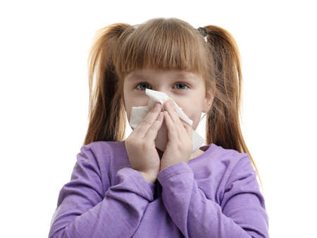 Cute little girl blowing nose against white background Stock Photo