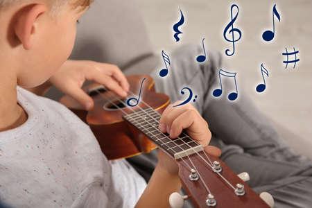 Niño tocando la guitarra en el sofá y notas musicales voladoras, primer plano