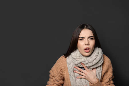 Beautiful young woman coughing against dark background. Space for text Foto de archivo