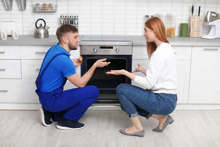 Housewife with repairman near modern oven in kitchen Stock fotó - 120157612
