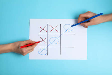 Women playing tic-tac-toe on color background, top view. Victory concept Stok Fotoğraf