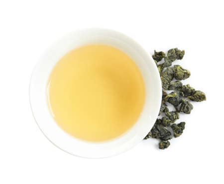 Cup of Tie Guan Yin oolong and tea leaves on white background, top view