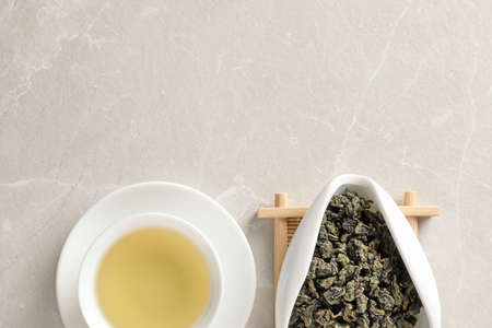 Cup of Tie Guan Yin oolong and chahe with tea leaves on table, top view. Space for text