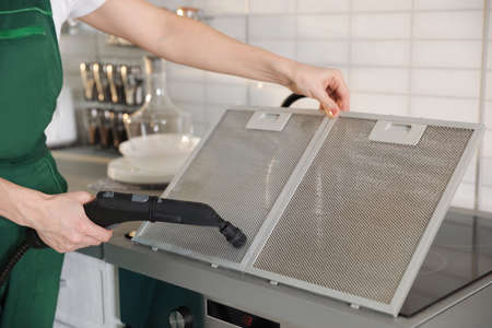 Professional janitor cleaning mesh filter of cooker hood in kitchen, closeup