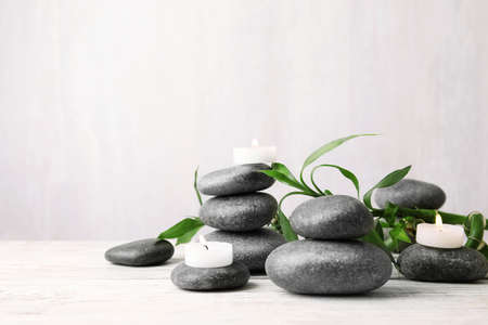 Composition with zen stones, bamboo and lighted candles on table against light background. Space for text