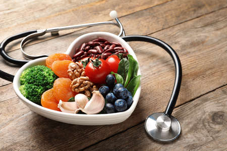 Bowl with heart-healthy diet products and stethoscope on wooden table. Space for text