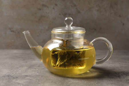 Glass teapot with oolong on table against grey background