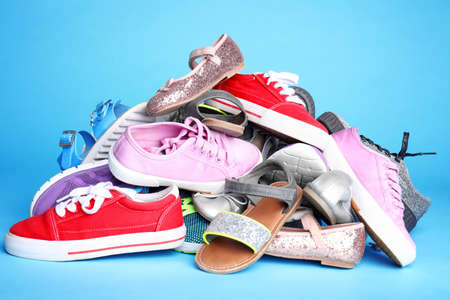 Heap of different shoes on color background 版權商用圖片