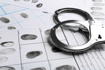 Handcuffs and fingerprint record sheets, closeup. Criminal investigation