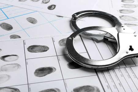 Handschellen und Fingerabdruckprotokolle, Nahaufnahme. Strafrechtliche Ermittlung