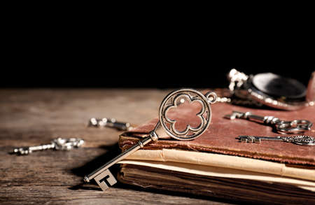 Old vintage keys with book and antique watch on wooden table, space for text
