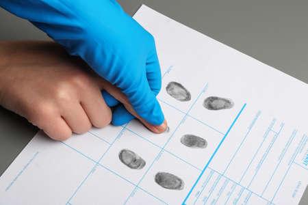 Investigator taking fingerprints of suspect at table, closeup. Criminal expertise 스톡 콘텐츠