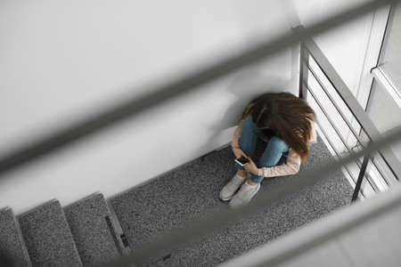 Upset teenage girl with smartphone sitting on staircase indoors, above view