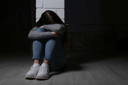 Upset teenage girl sitting at column indoors. Space for text